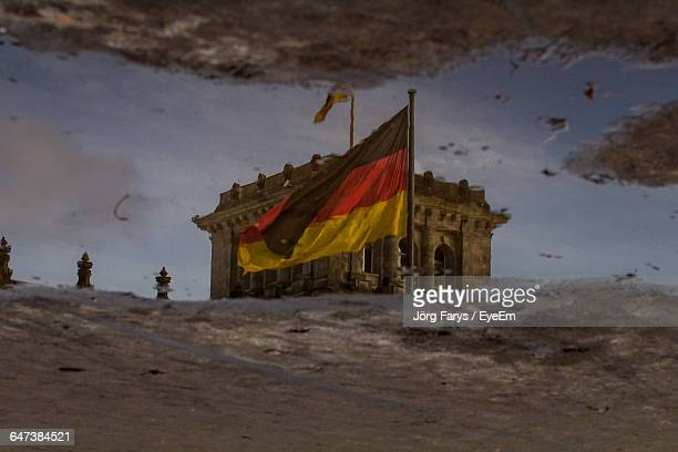 Reflection Of Reichstag Building And German Flag In Puddle On Street