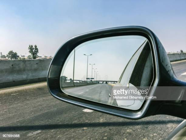 reflection of road on side-view mirror against sky - side view mirror stock photos and pictures