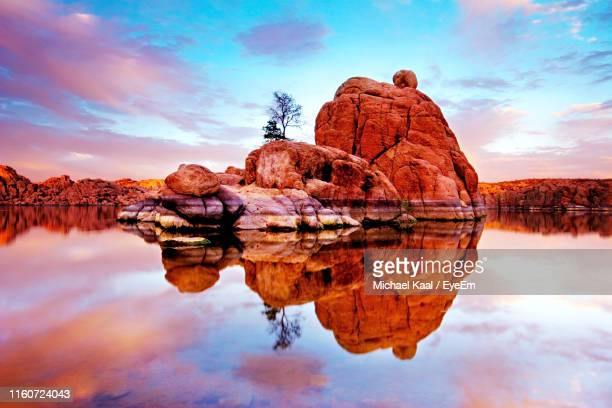 reflection of rock formation in lake against sky during sunset - kaal stock pictures, royalty-free photos & images