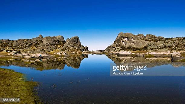 reflection of rock formations in lake against clear blue sky - cari stock pictures, royalty-free photos & images