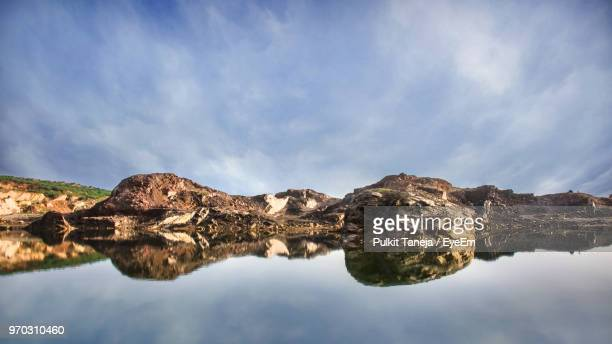 reflection of rocks in lake against sky - faridabad stock pictures, royalty-free photos & images