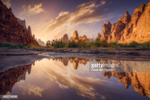reflection of rocks in water at sunset - saudi stock pictures, royalty-free photos & images