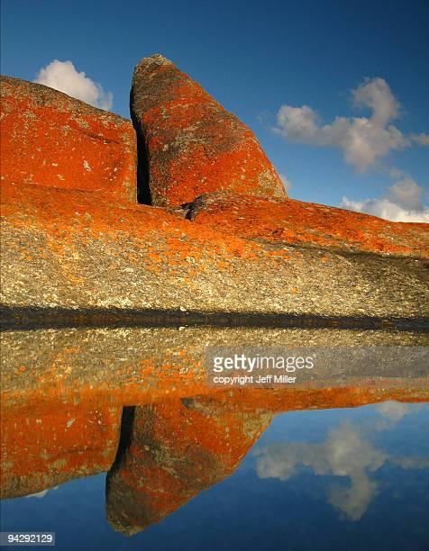 Reflection of rocks with orange lichen, blue sky