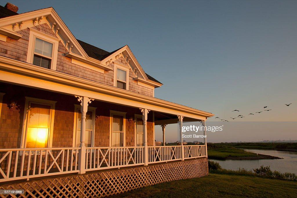 Reflection of setting sun on windows of cottage : Stockfoto