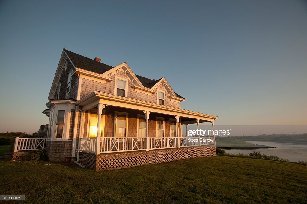 Reflection of setting sun on windows of cottage : Bildbanksbilder