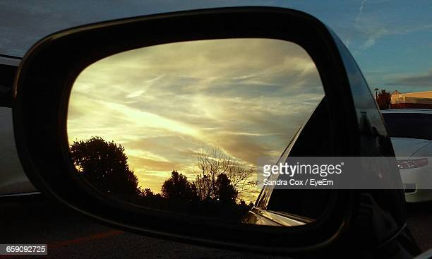 Reflection Of Silhouette Trees Against Cloudy Sky On Side-View Car Mirror At Sunset