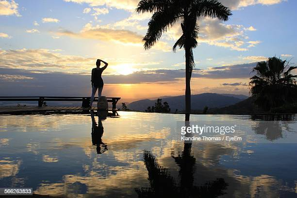 reflection of silhouette woman on lake at sunset - kingston jamaica stock pictures, royalty-free photos & images