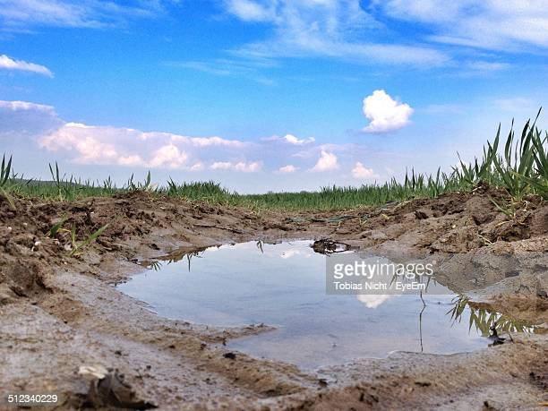 reflection of sky and clouds in puddle - puddle stock pictures, royalty-free photos & images