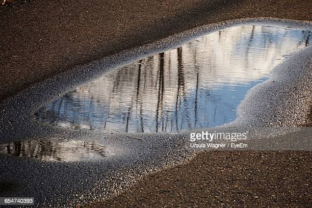 Reflection Of Sky And Clouds In Water Puddle On Road