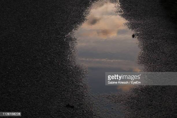 reflection of sky on puddle - sabine kriesch stock-fotos und bilder