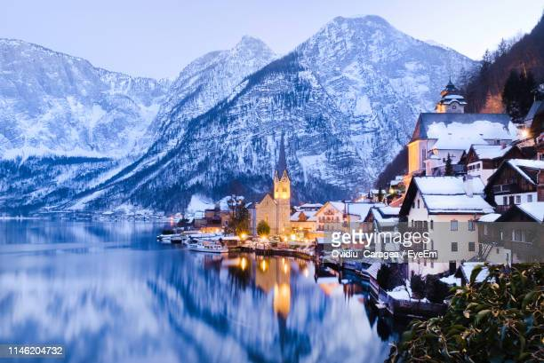 reflection of snowcapped mountains in lake - hallstatt stock pictures, royalty-free photos & images