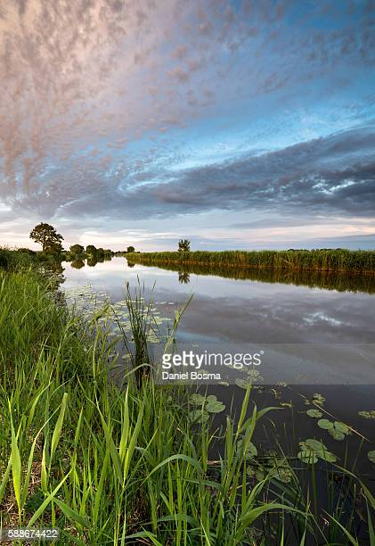 Reflection of spectacular sky in a Dutch canal during a quiet summer evening