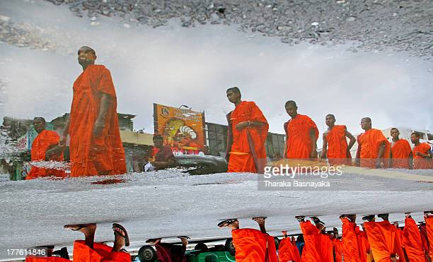 CONTENT] Reflection of Sri Lankan Buddhist monks from Singhala Ravaya organization parading in a street is seen on a water puddle on the road during...