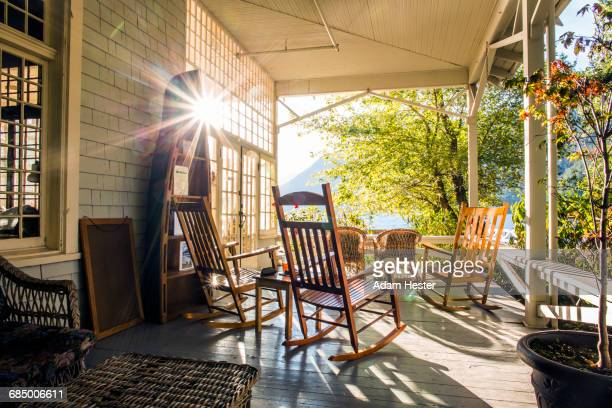 reflection of sun on porch with rocking chairs - rocking chair stock pictures, royalty-free photos & images