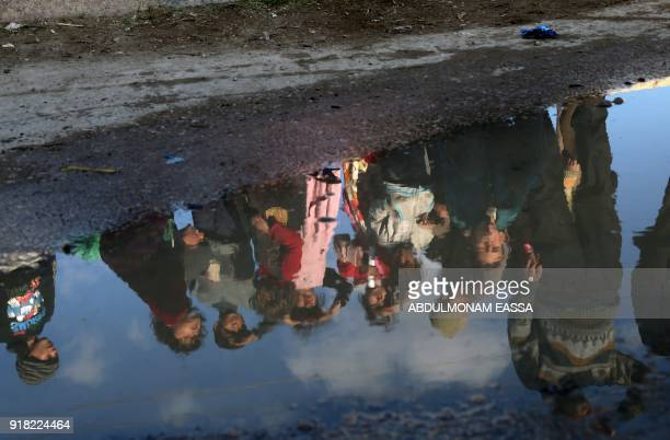 Reflection of Syrian children is seen in a puddle of water as they watch a United Nations and Syrian Red Crescent inter-agency convoy delivering aid...
