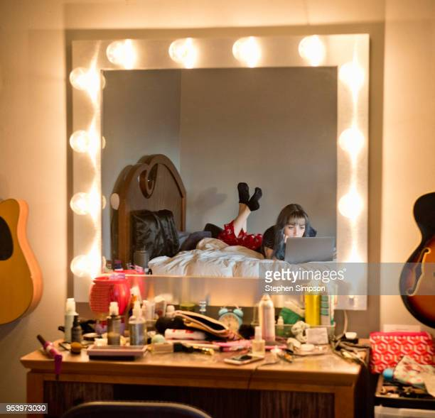 reflection of teen on laptop on bed - vanity stock pictures, royalty-free photos & images