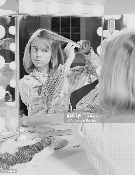reflection of teenage girl in lighted make up mirror, putting rollers in her hair. - krulspelden stockfoto's en -beelden