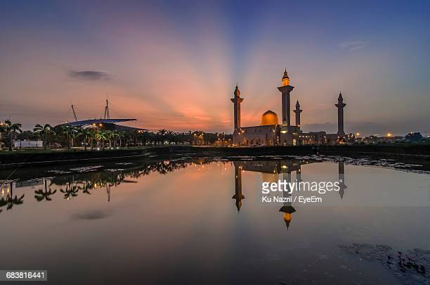 Reflection Of Tengku Ampuan Jemaah Mosque In Lake Against Sky During Sunrise
