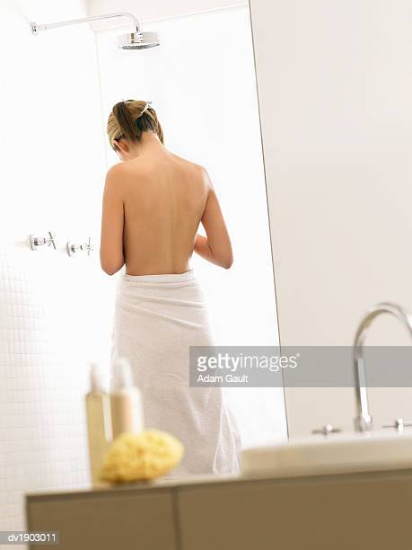 Reflection of the back of a Woman Standing by a Shower in a Bathroom