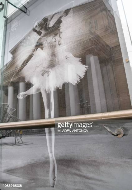 A reflection of the Bolshoi Theatre is seen on a poster of the famous Russian ballerina Marina Kondratieva in Moscow on December 6 2018