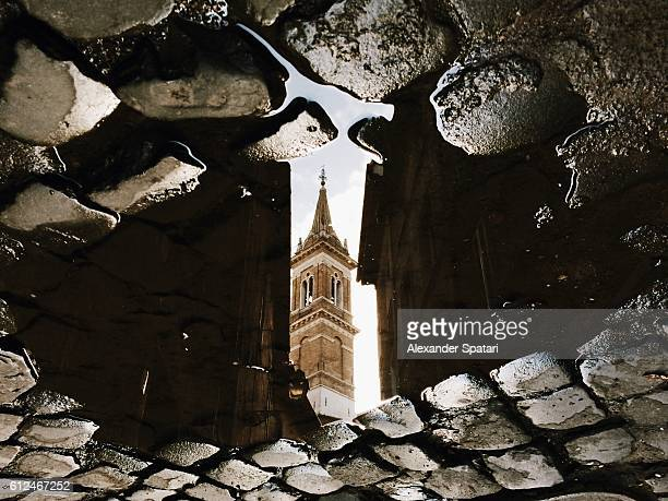 reflection of the church in puddle, rome, italy - atheism stock photos and pictures