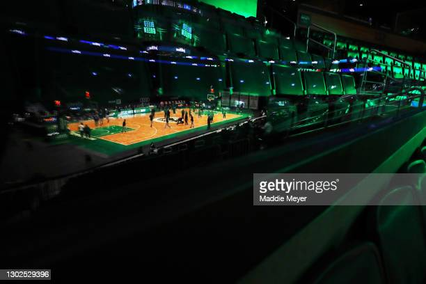 Reflection of the Denver Nuggets and the Boston Celtics warming up before their game, surrounded by empty seats, at TD Garden on February 16, 2021 in...