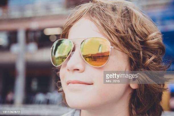 reflection of the guggenheim museum in a boy's sunglasses, bilbao, spain - guggenheim museum bilbao stock-fotos und bilder