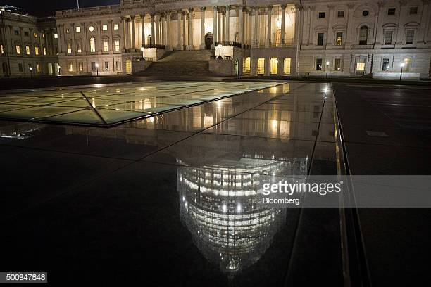 Reflection of the illuminated dome of the U.S. Capitol building is seen before sunrise in Washington, D.C., U.S., on Friday, Dec. 11, 2015. The...