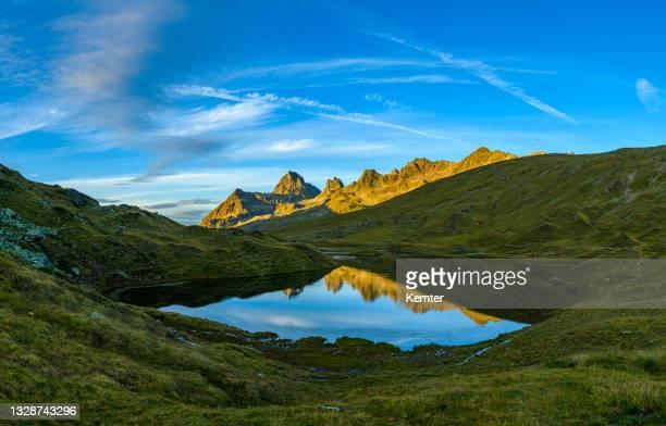 reflexion der berge in einem wunderschönen kleinen see bei sonnenuntergang - kemter stock-fotos und bilder