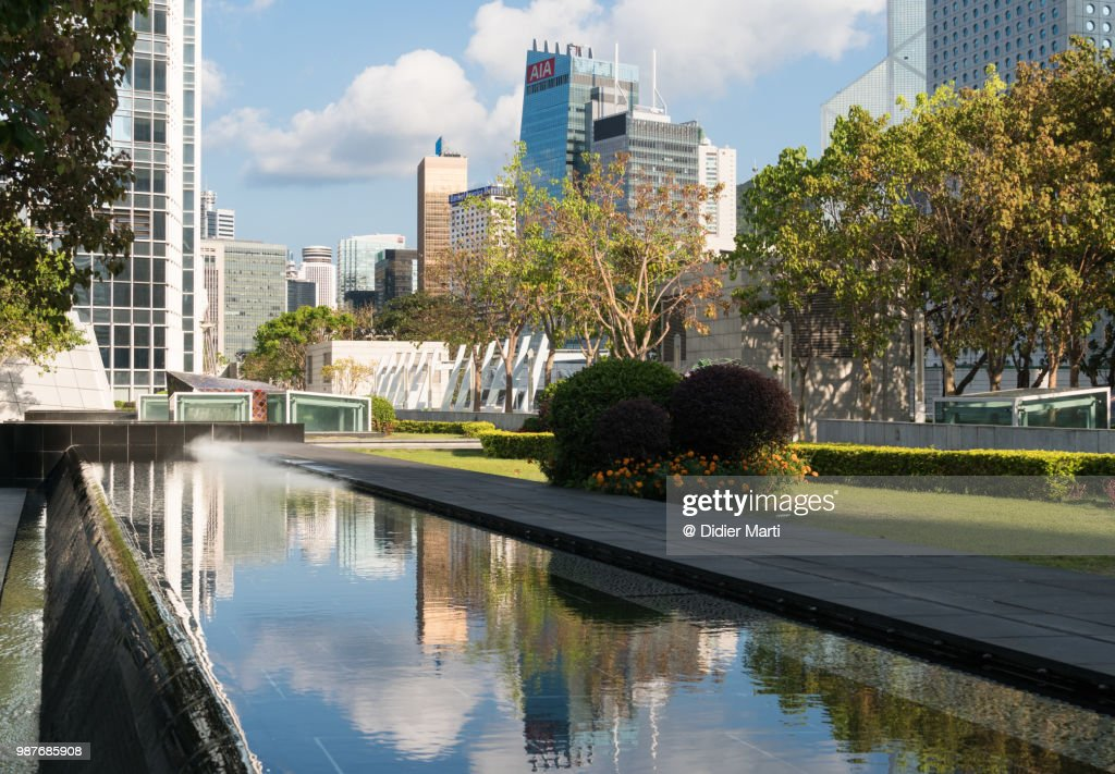 Reflection of the skyscrapers of the Central business district in Hong Kong island in the water of a pond : Stock Photo