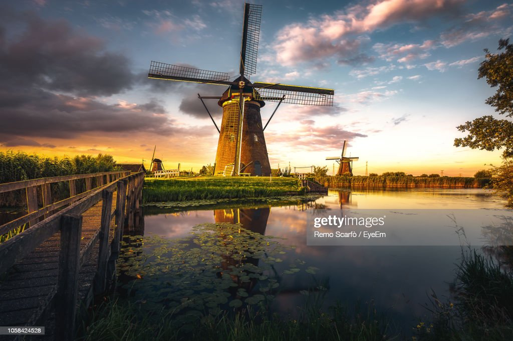 Reflection Of Traditional Windmill In Lake During Sunset : Stock Photo