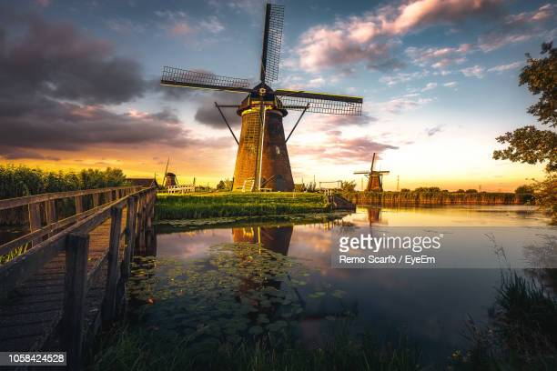 reflection of traditional windmill in lake during sunset - nederland stock pictures, royalty-free photos & images