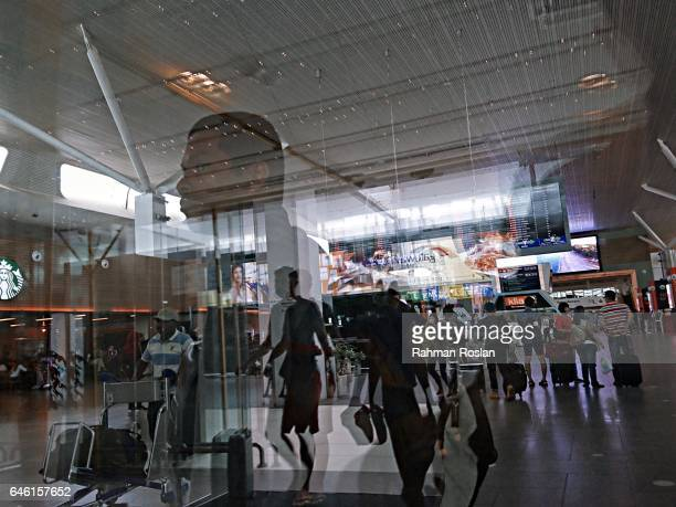 Reflection of travellers is seen throught the glass entrance door of The Kuala Lumpur International Airport 2 terminal in Kuala Lumpur International...