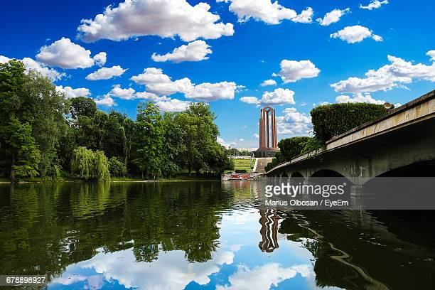 Reflection Of Trees And Bridge On River Against Blue Sky