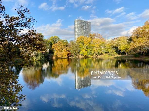 reflection of trees and buildings in lake against sky - klaus-dieter thill stock-fotos und bilder