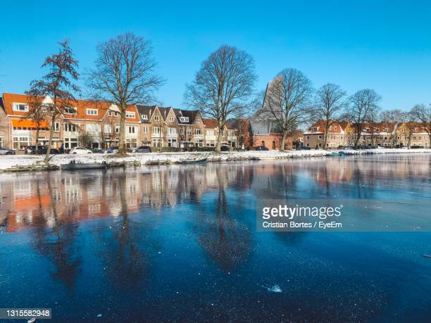 reflection of trees and buildings in lake - bortes stock pictures, royalty-free photos & images