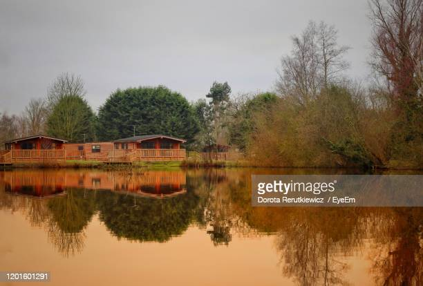 reflection of trees and house in lake against sky - king's lynn stock pictures, royalty-free photos & images