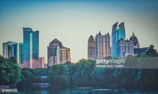 reflection of trees in lake against buildings in midtown atlanta - atlanta stock pictures, royalty-free photos & images