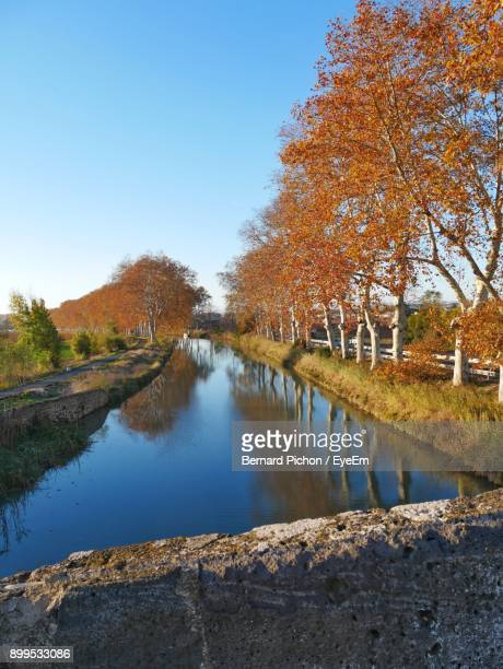reflection of trees in lake against clear sky - canal du midi photos et images de collection
