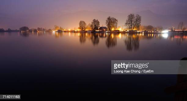 reflection of trees in lake against sky at sunset - kashmir valley stock photos and pictures