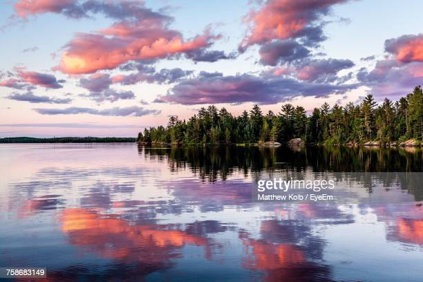 reflection of trees in lake against sky during sunset - minnesota foto e immagini stock