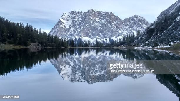 Reflection Of Trees In Lake Against Snowcapped Mountains