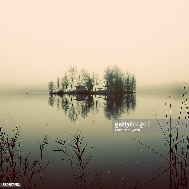 Reflection Of Trees In River Against Sky During Foggy Weather