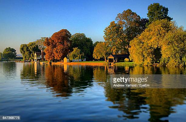 Reflection Of Trees In River During Autumn Against Clear Blue Sky