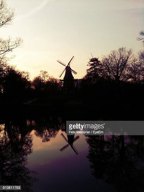 Reflection of windmill and trees on lake during sunset against clear sky