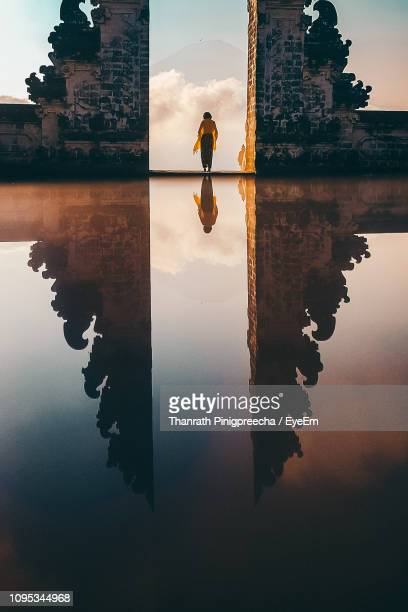 reflection of woman amidst built structure on lake against sky - bali foto e immagini stock
