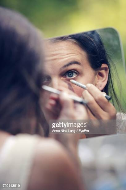 reflection of woman applying eyeliner on mirror - eye liner stock photos and pictures