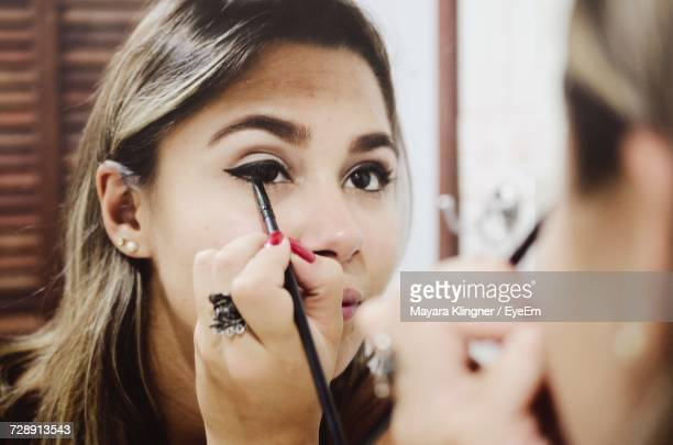 reflection of woman applying eyeliner on mirror - applying stock pictures, royalty-free photos & images