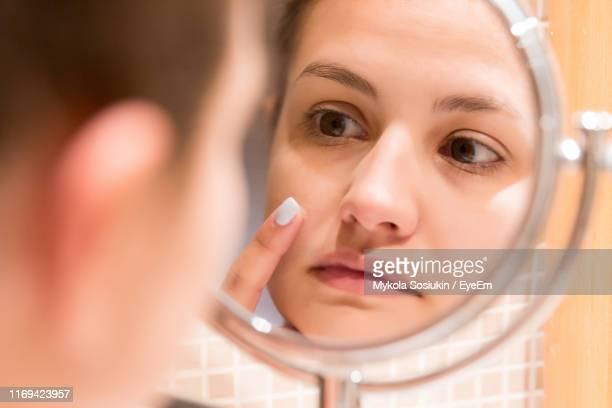 reflection of woman applying moisturizer on pimple in mirror at home - pimple stock pictures, royalty-free photos & images