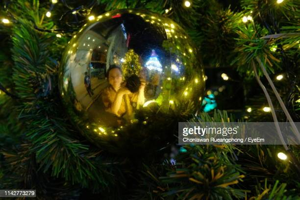 Reflection Of Woman In Bauble On Illuminated Christmas Tree At Night
